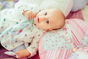 Criança de cabelos curtos deitada na cama