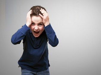 Criança gritando com as mãos na cabeça