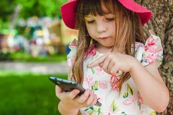 Criança que joga com um celular