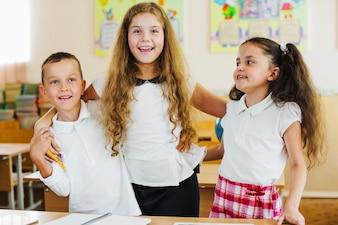 Crianças em camisa branca abraçando posando