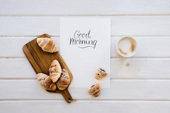 Croissants, caneca de café e modelo