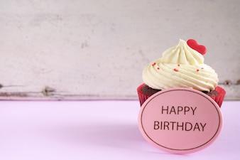 Cupcake do aniversário com coração vermelho