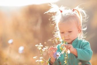 Cute e doce menina brincando com flores ao ar livre