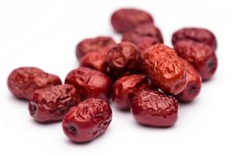 Data vermelha secada ou jujuba chinês. Derramamento tradicional da medicina de erva na esteira.