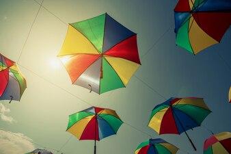 Decoração colorida de rua guarda-chuva com luz solar. Tom do vintage.