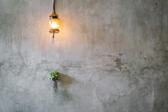 Decoração da iluminação do vintage com a planta sobre a parede do cimento.