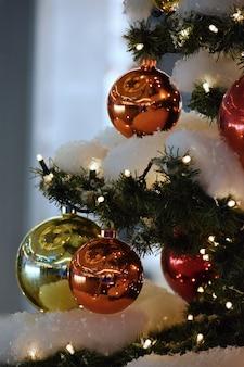 Decoração de Natal colorida. Férias de inverno e ornamentos tradicionais em uma árvore de Natal. Cadeias de iluminação - velas para fundo sazonal.
