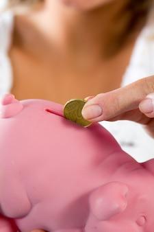 Dedos colocando 20 centavos de dólar no banco piggy