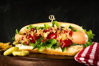 Descrição da foto: Cão quente americano clássico saboroso com salsichas e ketchup na placa de madeira.