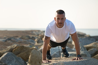 Desportivo atleta bonito se preparando para flexões