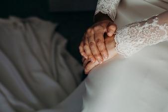 Detalhe de mãos de noiva e vestido de noiva antes da cerimônia.