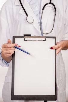 Detalhe de um médico com estetoscópio segurando uma prancheta