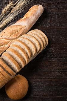 Diferente pão fresco, na velha mesa de madeira, tom escuro