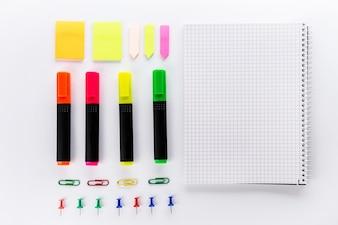 Diferentes marcadores coloridos com acessórios de escritório na mesa de escritório branco. Vista do topo. Conceito de estudo de trabalho. Flat Lay.