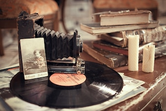 Disco de vinil, com uma câmera velha e alguns livros antigos