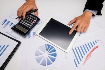 Documentos de negócios na mesa do escritório com telefone inteligente e tablet digital e homem trabalhando em segundo plano.