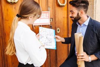 Dois agentes imobiliários em frente a uma porta