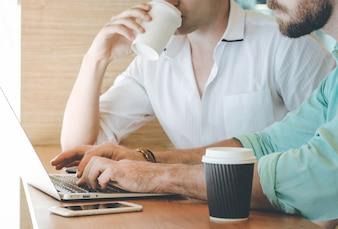 Dois empresários reunião e uso de laptop com smartphone no café