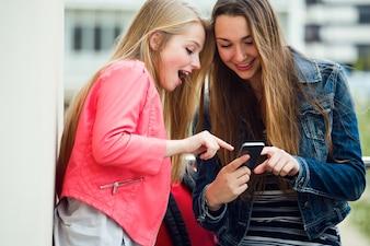 Dois estudantes bonitos usando o celular na rua.