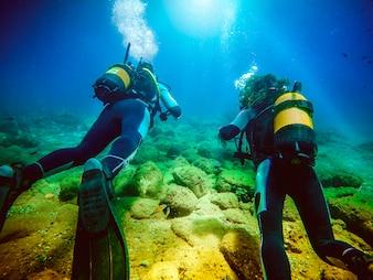 Dois mergulhadores nadando longe da câmera.