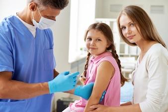 Doutor que injeta vacina a menina