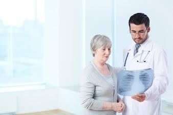 Doutor que mostra um raio-x ao paciente idoso