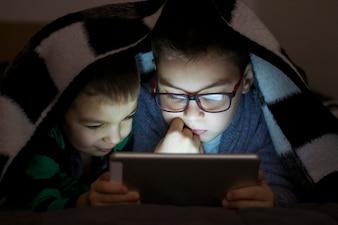 Duas crianças usando tablet pc sob cobertor durante a noite. Irmãos bonitos com tablet computador em um quarto escuro sorrindo.