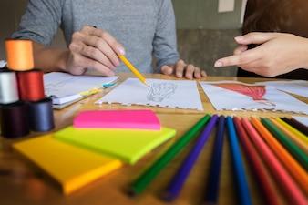 Duas jovens trabalhando como estilistas e desenhando esboços e obtêm conselhos de tecido em um alfaiate personalizado