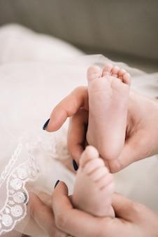 Duas mãos segurando os pés do bebê
