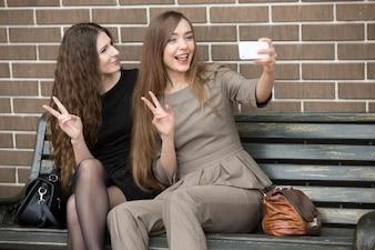 Duas mulheres jovens lindas que tomam um selfie na rua