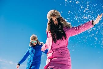 Duas namoradas se divertem e aproveitam a neve fresca em um belo dia de inverno nas montanhas