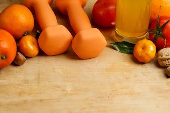 Dumbbell, suco de laranja, frutas e nozes na mesa de madeira, esporte e conceito de estilo de vida saudável