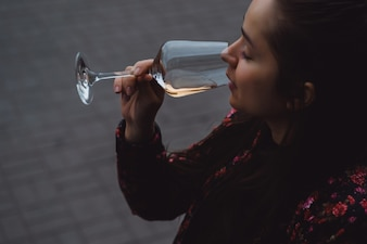Elegante jovem bebe vinho em um café de rua em um terraço de verão. Uma menina com cabelos longos goza de um copo de vinho na noite de verão. Retrato. fechar-se