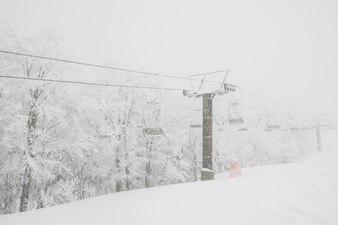 Elevador de esqui sobre a montanha da neve na estância de esqui.