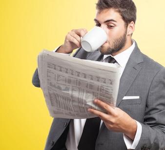 Empregado bebendo café enquanto lê o jornal