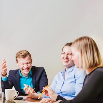 Empregados do escritório sentados na mesa, sorrindo