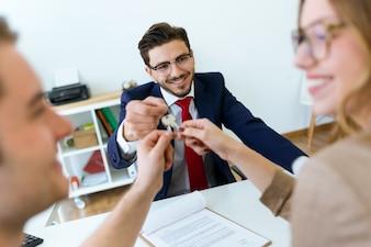 Empresário entrega as chaves da casa para um casal depois de fechar a venda.