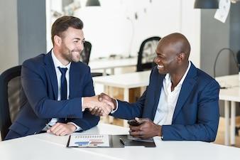 Empresário preto apertando as mãos com um caucasiano no escritório