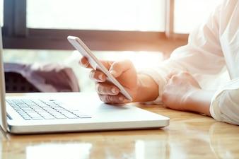 Empresário usando laptop e celular.