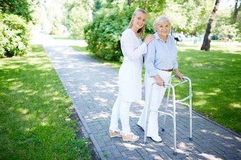 Enfermeira que ajuda a mulher sênior a usar o frame de passeio