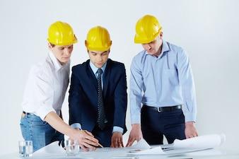 Engenheiros com capacetes de rever o esboço