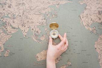 Entregue a colocação de uma bússola sobre um mapa do mundo
