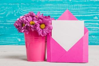 Envelope rosa com pedaço de papel e flores roxas decorativas