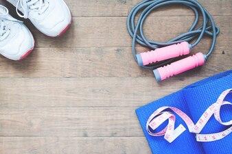 Equipamentos esportivos e de ioga com fita métrica em fundo de madeira com espaço de cópia
