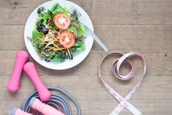 Equipamentos esportivos, salada fresca e fita métrica em forma de coração, conceito de estilo de vida saudável