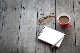 Espaço de cópia do caderno vazio e xícara vermelha de café no fundo de madeira
