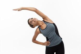 Esporte, treinamento, estilo de vida e conceito de Fitness - retrato da bela mulher afro-americana feliz esticando as mãos. Isolado no fundo branco do estúdio.