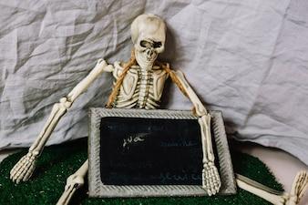 Esqueleto sentado com quadro-negro