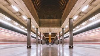 Estação de metrô e dois metrô em movimento