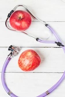 Estetoscópio médico e uma fruta da maçã sobre o fundo de madeira. Imagem do conceito do estilo de vida saudável.
